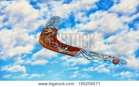 Multicolored australian boomerang in flight against of blue sky and pure white clouds.