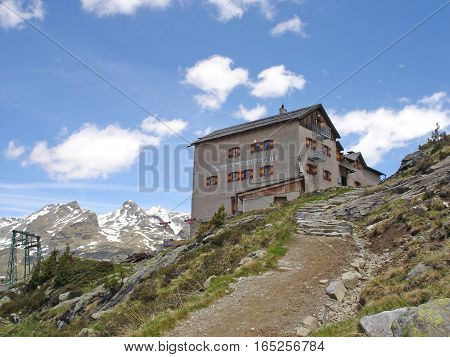 View of the Kassel hut and snow-capped mountains, the hut is located in the Nature Park Rieserferner-Ahrn in South Tyrol, Italy