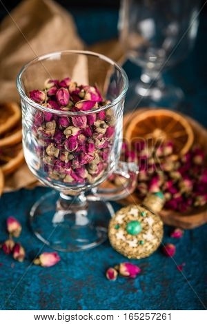Dry tea rose buds in a glass on dark blue background