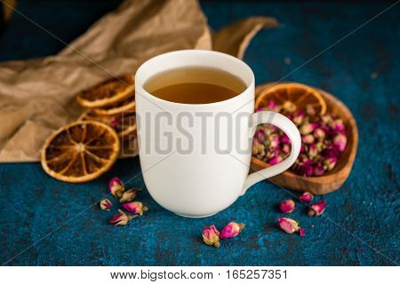 Cup of herbal tea and dry flower buds of rose on dark blue background