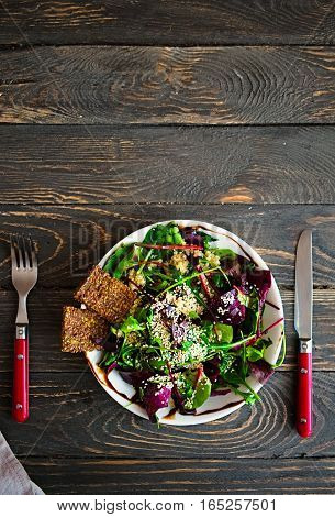 Fresh green salad with spinach arugula quinoa and flex seed crackers on a dark wooden table. Healthy food lifestyle concept. Flat lay. Copy space for text
