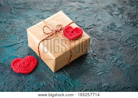 Gift boxes and crochet valentine hearts on dark background.
