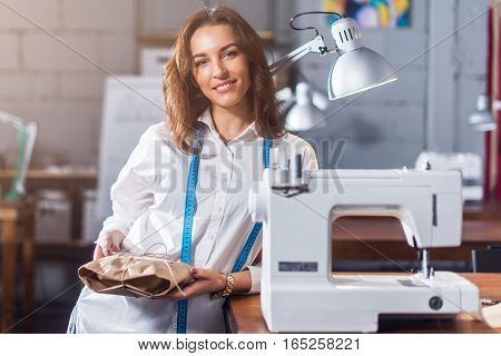 Portrait of smiling European fashion designer standing next to sewing machine holding a gift packed in craft paper in studio.