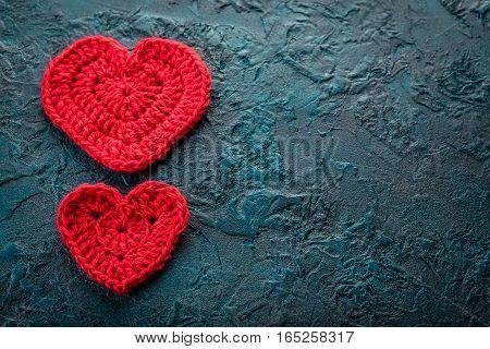 Two crochet valentine hearts on dark bacground.