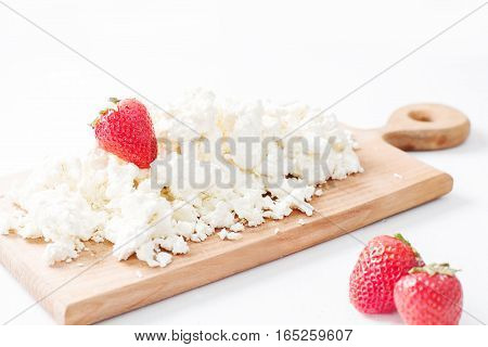 Cottage cheese with strawberries on a wooden board on a light background