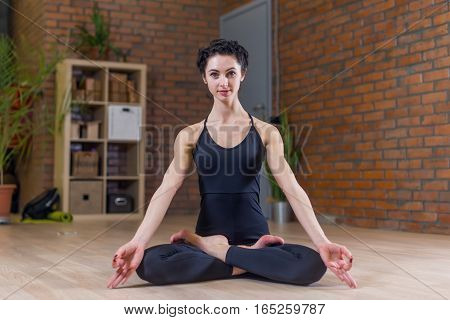 Woman sitting in lotus position doing yoga indoors at home.