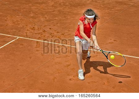 Young woman playing tennis backhand stroke, toned image