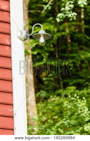 Closeup Of Lamp On Wooden House In Forest