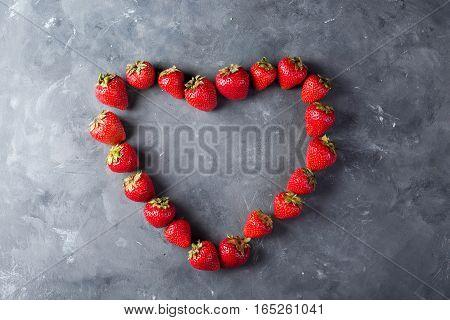 Valentine's Day background. Fresh strawberries array heart shape on dark background. Copyspace.