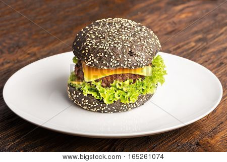 burger with beef cutlet with vegetables sesame seeds on slate board on wooden background