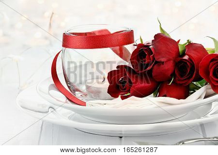 Romantic candlelite table setting with long stem red roses and candles in the background. Shallow depth of field with selective focus on roses.
