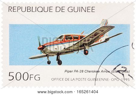 MOSCOW RUSSIA - January 11 2017: A stamp printed in Guinea shows aircraft Piper PA-28R-180 Cherokee Arrow in flight series