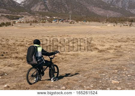 The guy sitting on BMX and looking at the rest of the mountain. Winter.
