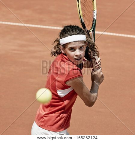 Teenage tennis player hitting backhand, toned image