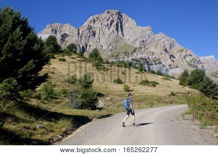 Guy Walking With A Range Mountain Behind Him