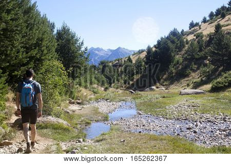 Mountaineer Hiking In The Mountain With A Steam Close To Him In Pyrenees, Spain