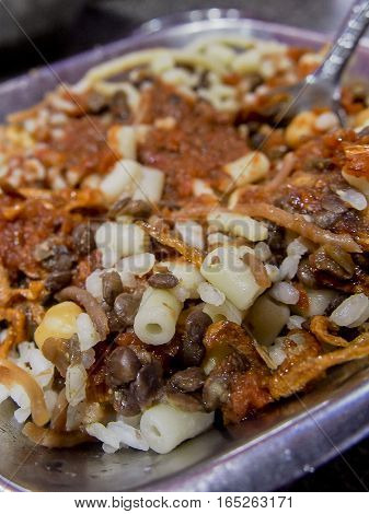 Koshari is a popular and cheap Egyptian dish made of lentils, rice, and pasta in a tomato-based sauce.