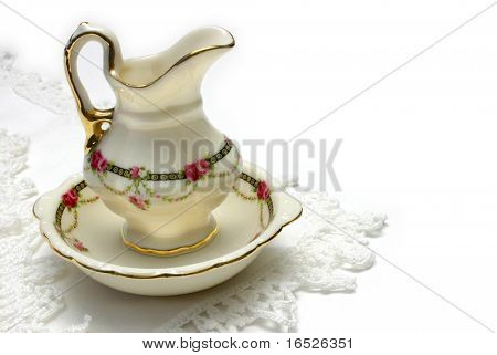 Miniature antique style wash basin and jug on crochet edged linen, isolated on white