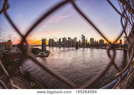 Brooklyn bridge and downtown skyline in New York. Manhattan skyscrapers seen through a fence on Manhattan bridge at dusk. Travel and architecture concepts