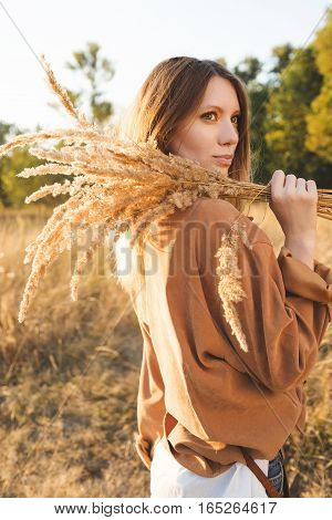 Beautiful blonde in blue jeans a white shirt and brown jacket posing in a field and holding a bouquet with spikelets. Boho style