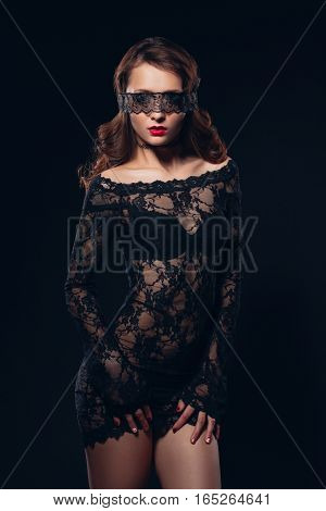 Sexy girl in black lingerie on black background. Erotic photoshoot charming attractive woman with a blindfold mask on her face. Perfect ass and beautiful makeup poster