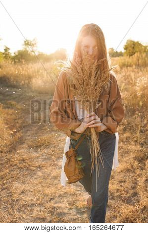Beautiful blonde in blue jeans a white shirt and brown jacket walking in the field laughing and holding a bouquet with spikelets. Boho style
