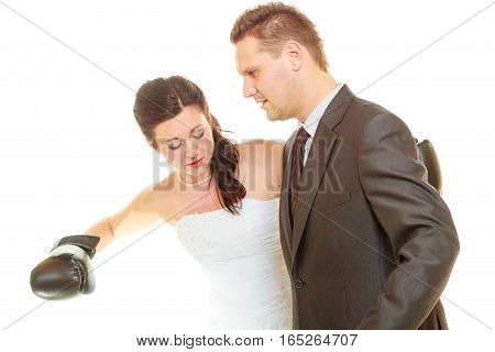 Conflict in relationship concept. Married couple fighting with each other. Woman wearing wedding dress and boxing gloves punching her husband in elegant suit.