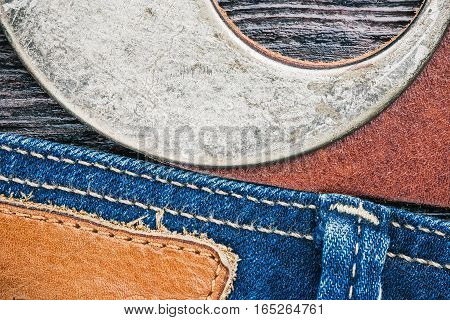 Blue jeans stitched edge and rusty leather belt combined background. Macro view