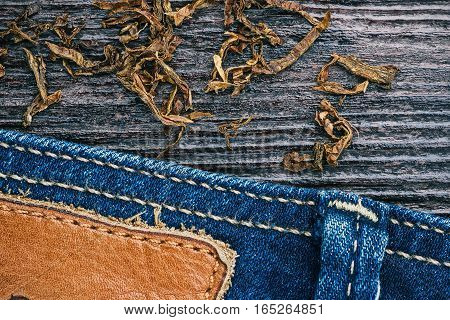 Blue jeans stitched edge and tobacco flakes on wood combined background. Macro view