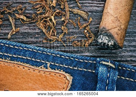 Blue jeans stitched edge, tobacco flakes and ashed cigar on wood. Macro view
