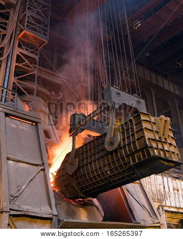 Loading converting furnace. Factory production of steel