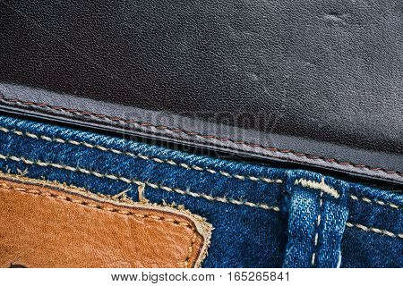 Blue jeans stitched edge and dark brown leather combined background. Macro view