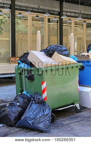 Overflow of Trash in Garbage Container and Black Bags