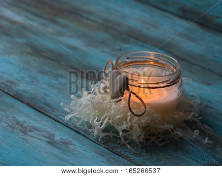 Composition of spa treatment candle on wooden background. Copy space.