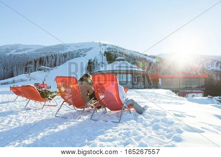 Chopok, Slovakia - January 12, 2017: Skiers And Snowboarders Taking A Rest In Chairs Near Apres Ski