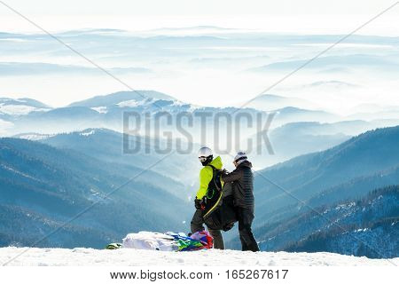 Paragliders Getting Ready To Launch From Snowy Slope Of A Mountain