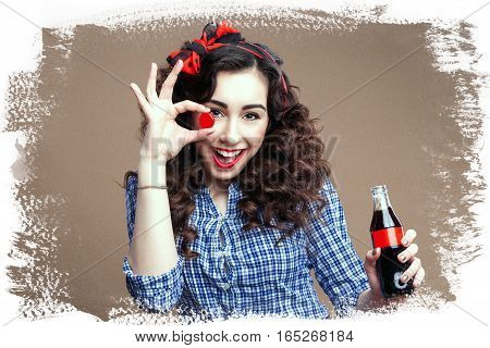 Playful pinup brunette holding cup of glass bottle. White brushed brown paper stylish background.
