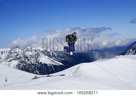 Snowboarder Jumping In Terrain Park At Snow Mountain On Sunny Winter Day