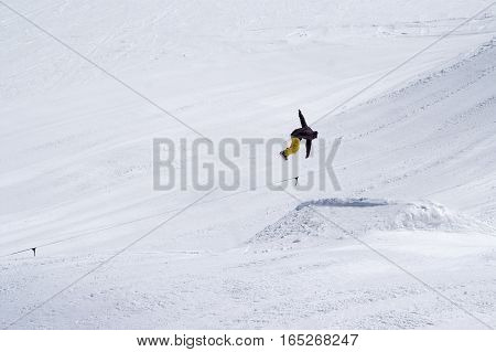 Snowboarder Jumping In Snow Park At Ski Resort On Sun Winter Day
