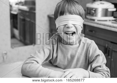 The child was blindfolded at home and want to make him surprise. Boy peeping from under the blindfold.
