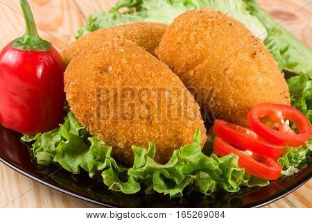 three fried breaded cutlet with lettuce on a black plate and a wooden background.