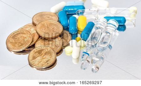 Pills capsules ampoules and coins on reflective background. Medical concept.