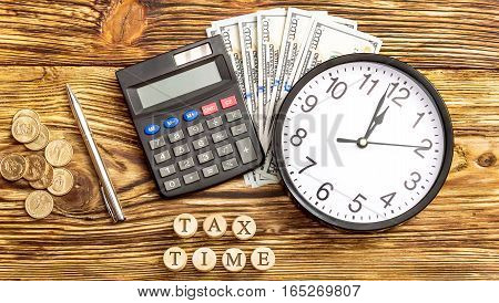 Time for tax. Calculator money clock and inscriptions on the wooden barells