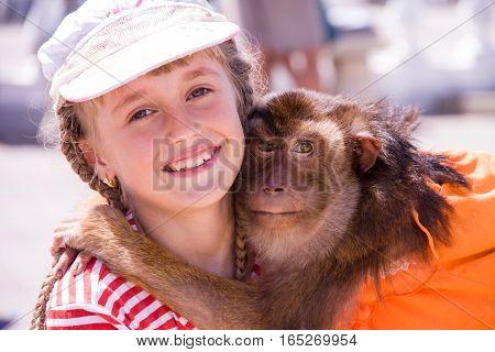 pet monkey hugging a girl on the street.