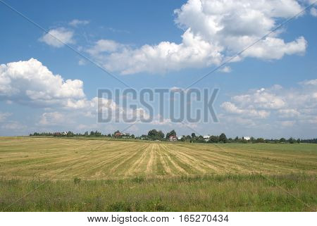 Countryside summer landscape with cultivated field and a village far away under cloudy sky
