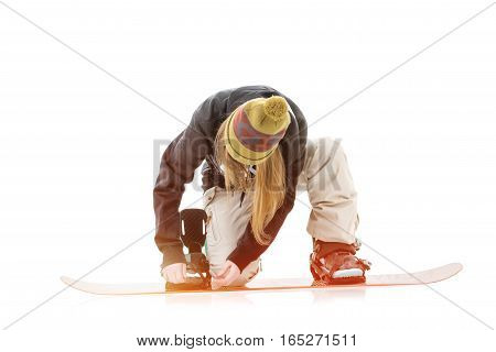 Young woman putting on snowboard on white background
