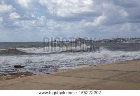 Taken on a visit to Paphos on a stormy windy day and shows large waves and cloudy skies.