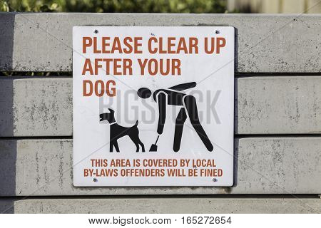 Please clear up after your dog. A written sign with an image of a responsible pet owner cleaning up after their dog.