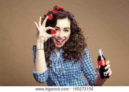 Smiling playful curly brunette holding cup and glass bottle. Girl clothed red scarf and plaid shirt. Pinup style.