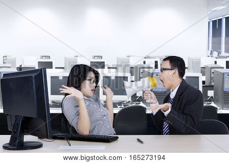 Portrait of an angry male manager shouting at his secretary through megaphone while working with a computer in the workplace